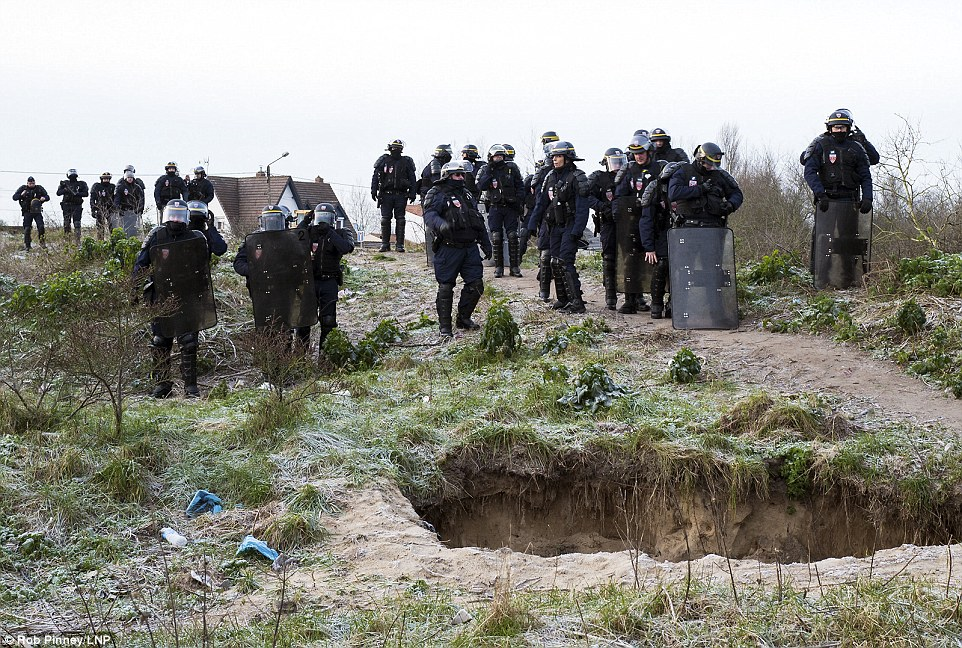 Big guns: French riot police prepare to enter the Calais 'Jungle' to evict up to one third of the camp on Monday morning