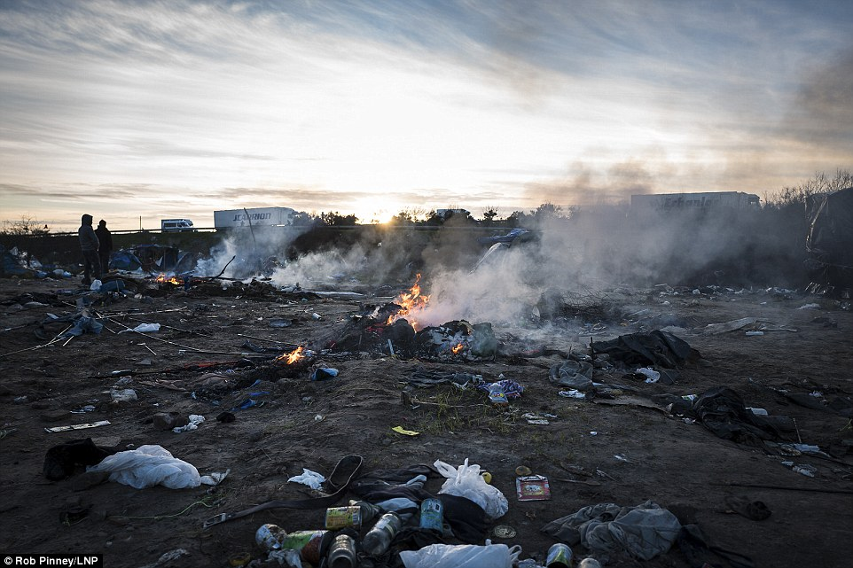 The jungle burns: Fires burn in an Afghan section of the Calais 'Jungle' which has been cleared ahead of a planned eviction on Monday morning, where bulldozers will clear about a third of the notorious camp