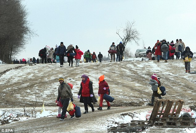 More than 12,000 people have been sent to other EU countries from Britain since 2003. Pictured: Migrants from Syria, Iraq and Afghanistan walk in very cold weather, through snow in Macedonia to a camp