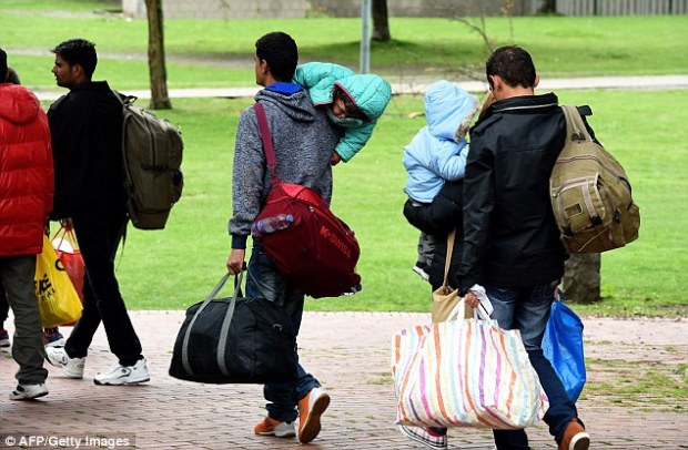 In the dark: The German government is unable to say where more than half of the one million asylum seekers allowed into the country have ended up. Migrants are pictured walking to get a bus after arriving in Dortmund