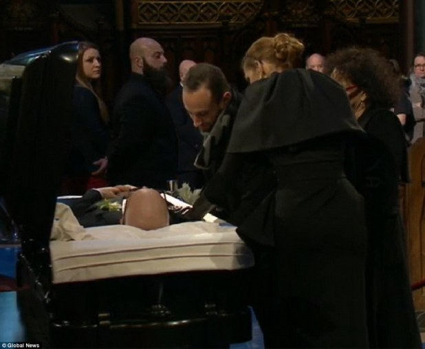 A touching moment: The Grammy winner laid her left hand on her late husband as family gathered near