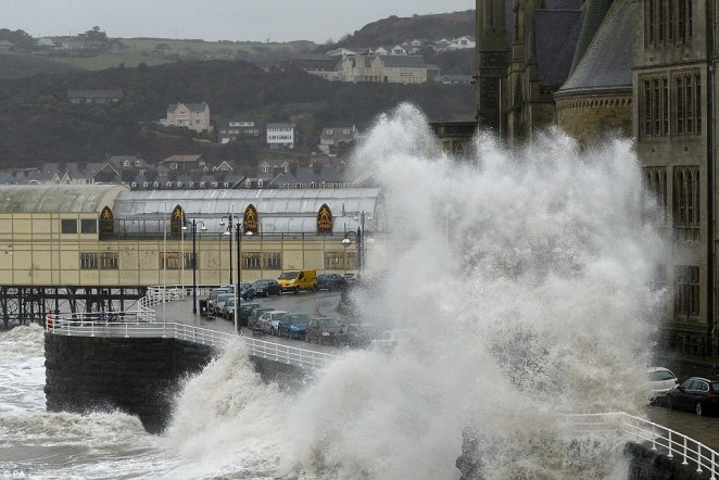 Battering the coasts:Waves crash against the the promenade in Aberystwyth as huge swathes of the UK experience more heavy rainfall