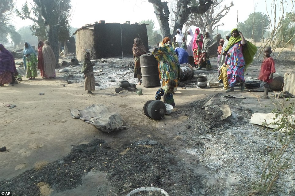 Devastated: Women and children search through debris in the village ofDalori after it was burnt to the ground by Boko Haram extremists