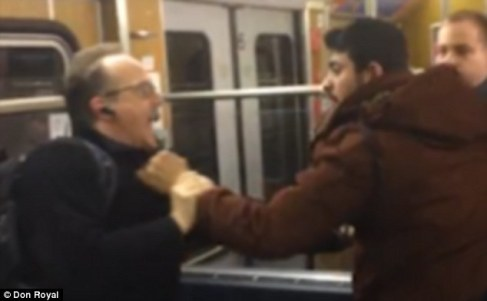Recorded on a mobile phone, the disgraceful video shows the men - of Eastern European or Arabic origin - holding one man by the arms as they verbally abuse him. The second victim is seen grappling with one of the migrants, before he is held up by the neck and threatened (pictured)