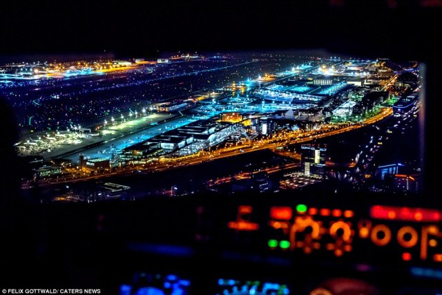 This image reveals a breathtaking shot of an airport at night as the large passenger plane makes its approach for landing