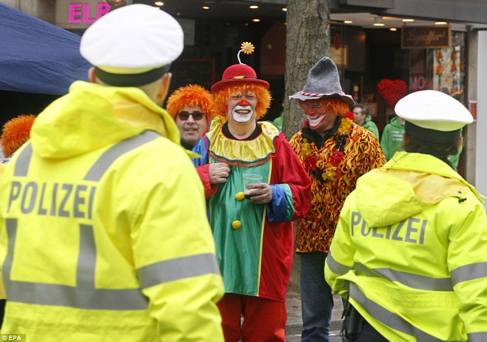 Los miembros de la policía alemana caminan más allá de la celebración de personas ataviadas con trajes de carnaval durante el 'Koe-Treiben' en Düsseldorf