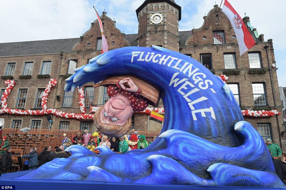 El ahogamiento: Una vista de flotación de una feria en Dusseldorf que representa la canciller alemana, Angela Merkel, en un barco con una bandera alemana se overfurned por un 'fluchtlingswelle' - ola de refugiados