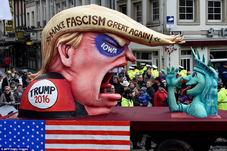 Trump triunfó: Otro flotador aparecía un enorme busto del candidato presidencial republicano Donald Trump - completa con un ojo negro para representar a su pérdida reciente en el caucus de Iowa - ser objeto de burla por la estatua de la libertad