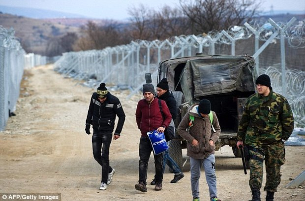A Macedonian Police officer turns back migrants, pictured, out of Macedonia at a checkpoint on the border line with Greece near the town of Gevgelija