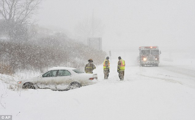 Firefighters from the Erie, Pennsylvania, Bureau of Fire prepare to leave the scene after checking on the occupants of a sedan that spun out in snowy conditions on Wednesday on the Interstate 79 northbound
