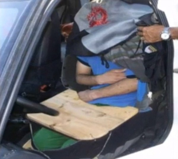Another man caught by Spanish police was found underneath a car seat cover while holding a flat board