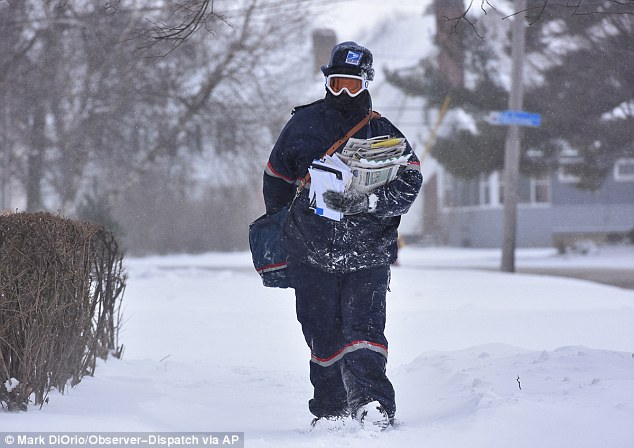 Jake Cote, a carrier with the United States Postal Service, delivers mail along in Utica, NY, on Thursday