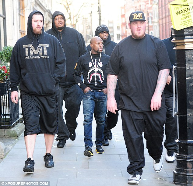 Boxing champ coming through: The 38-year-old was dwarfed by the stacked and towering minders who surrounded him as he made his way from one designer flagship to another