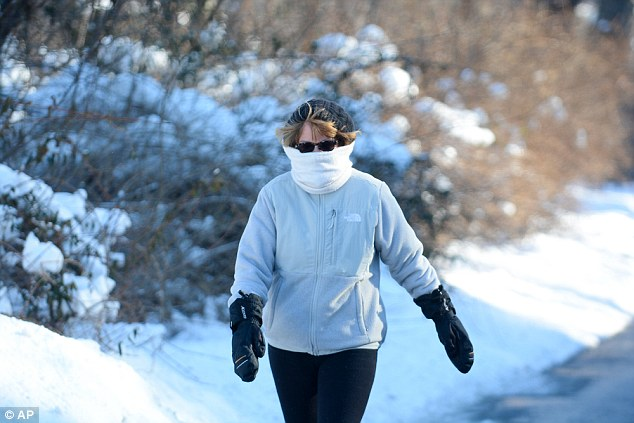Debbie Crosswell is bundled up as she braves below freezing temperatures and wind during her walk along Howard Avenue in Pottsville, Pennsylvania on Thursday