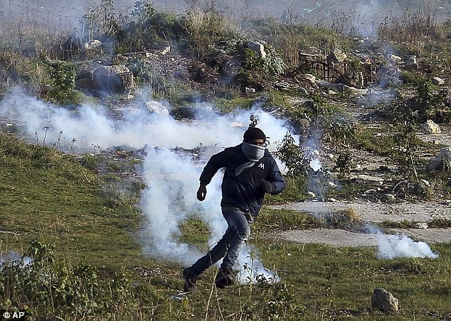 A migrant runs from tear gas thrown by police forces during a riot in the camp on January 21
