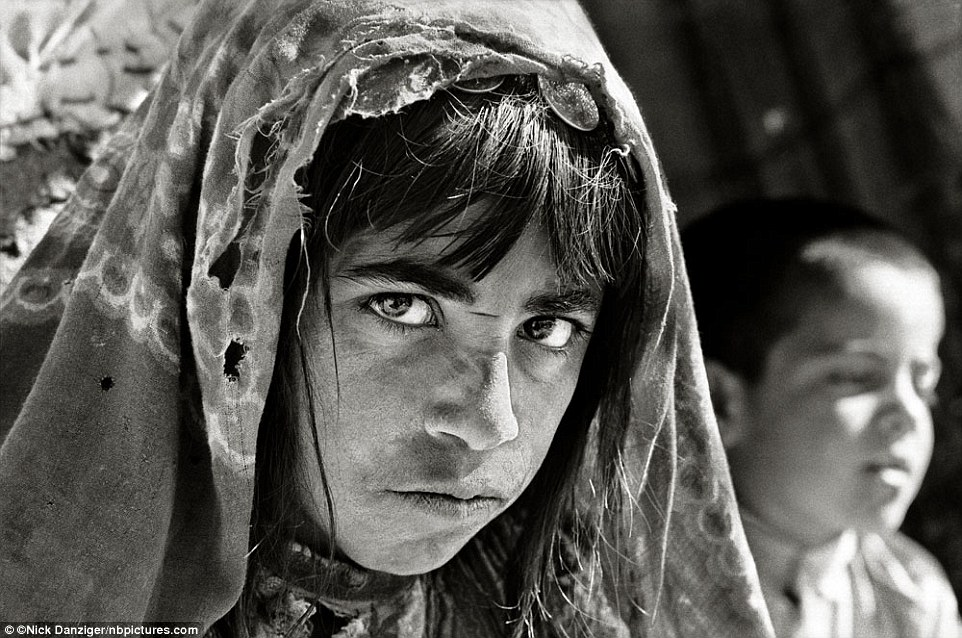 """Mah-Bibi, Afghanistan, 2001: 'My name is Mah Bibi. People tell me that I am ten-years-old. One of my brothers is five, the other seven. I am the """"head"""" of the family. Our parents are dead. People tell me there is war but I only think about hunger. I do not remember when my mother died - I was told my mother died in childbirth and it is four years since I lost my father. He went away. He said he was going to bring us food, but we haven't seen him since. We had two cows, ten sheep and some land but since my father went missing we were hungry so I sold all of them.'"""