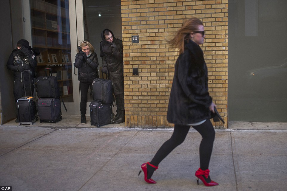 People shield themselves from the wind as a woman leaves after the Christian Siriano Fall 2016 show during New York Fashion Week on Saturday