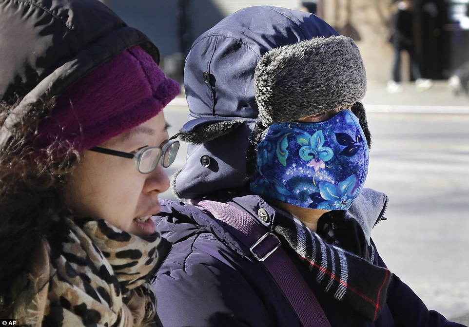 Women bundle up as they walk through the Queens borough of New York on Sunday as the city faced record-breaking lows