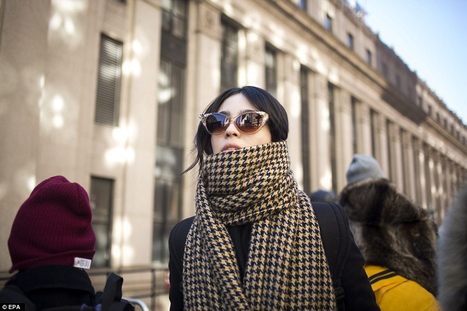 One woman dares to walk outside without a hat as she stands in the cold outside New York Fashion Week on Sunday