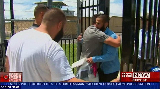 Dib (in blue) immediately hugged a male friend as he walked out from behind the prison gates
