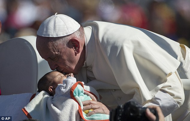 Pope Francis kissed the forehead of a number of babies as his popemobile inched through the large crowd
