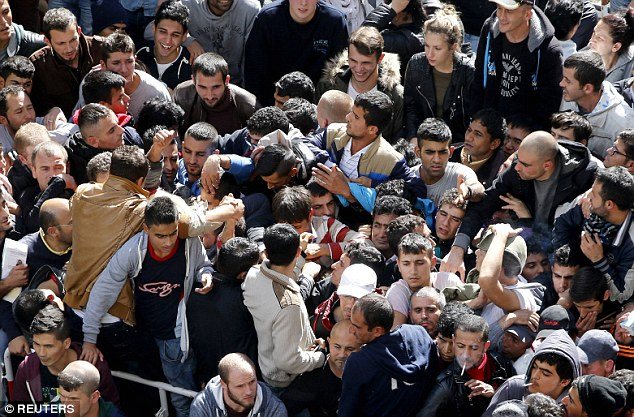 The German health service is facing a billion euro deficit due to the influx of healthcare needed for its booming migrant population. Pictured are a group of refugees in Berlin queuing for their registration papers
