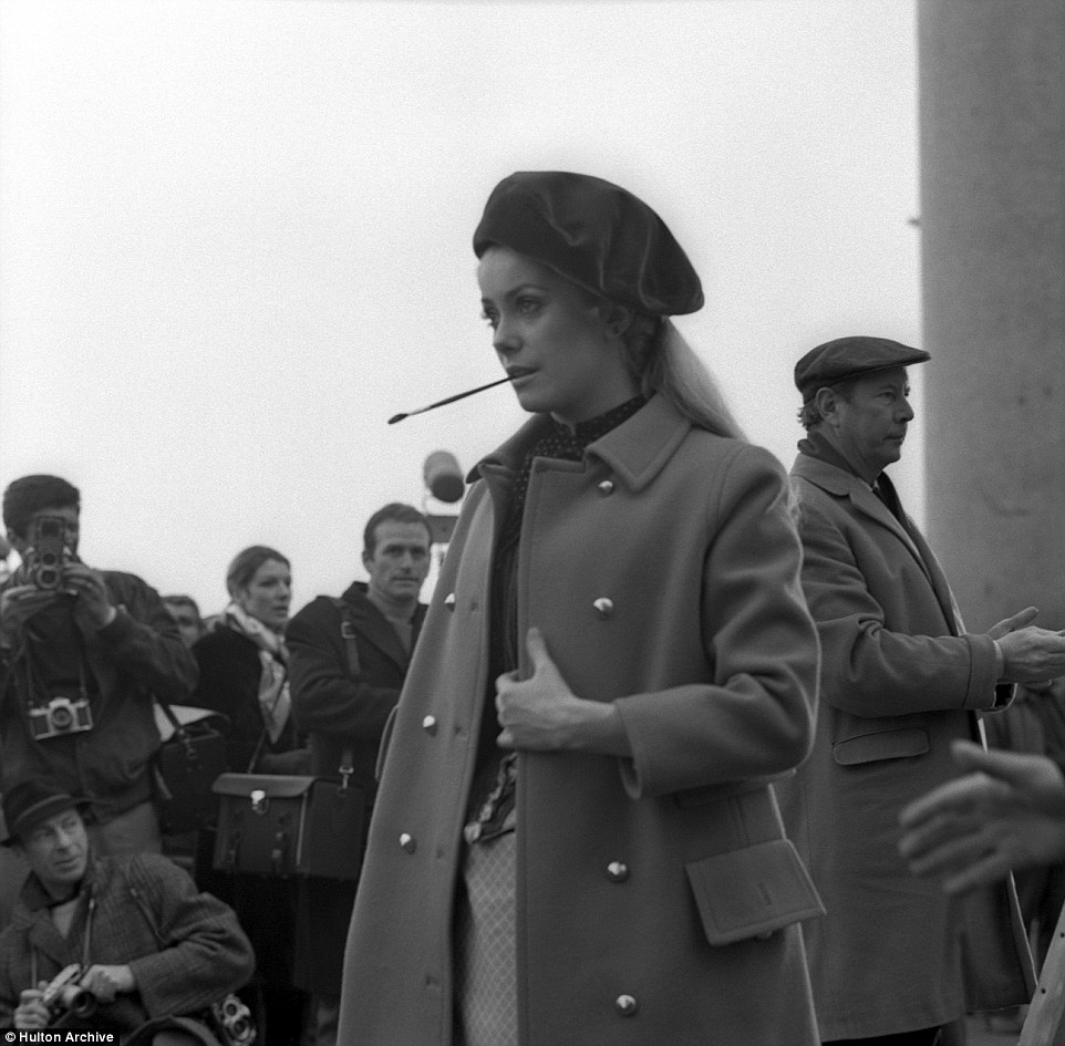 French actor Cathrine Deneuve on the set of the movie 'Mayerling', wearing a coat and and a beret. She holds a paintbrush in her mouth while photographers snaps away in March 1968