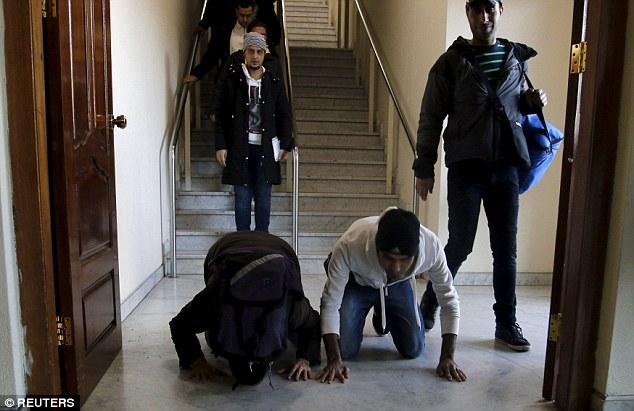 Dos inmigrantes iraquíes se arrodillan y besan el suelo después de llegar a la capital de Bagdad