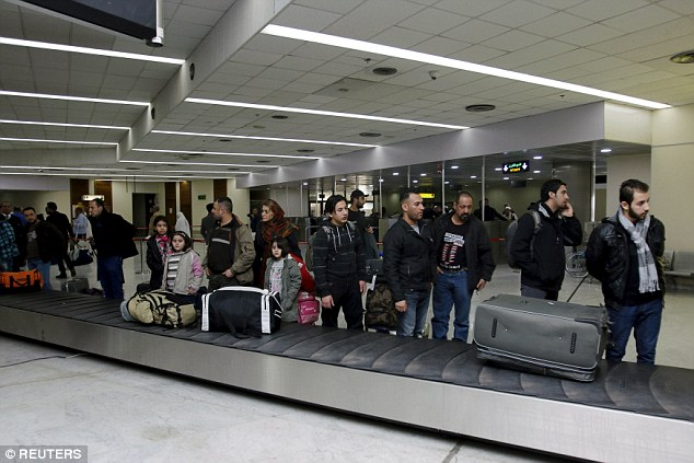 Los refugiados que solicitaron asilo en Finlandia pero regresaron voluntariamente a Irak esperan en la zona de recogida de equipajes