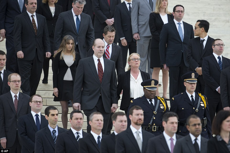 The family of Supreme Court Justice Antonin Scalia walk to greet the hearse as it arrives at the Supreme Court in Washington, DC