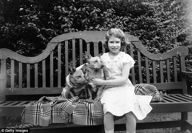 July 1936: Princess Elizabeth sitting on a garden seat with two corgi dogs at her home in London
