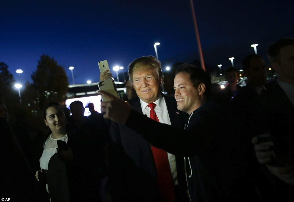 Say cheese: Republican presidential candidate Donald Trump takes a selfie with a supporter at a Las Vegas  caucus site