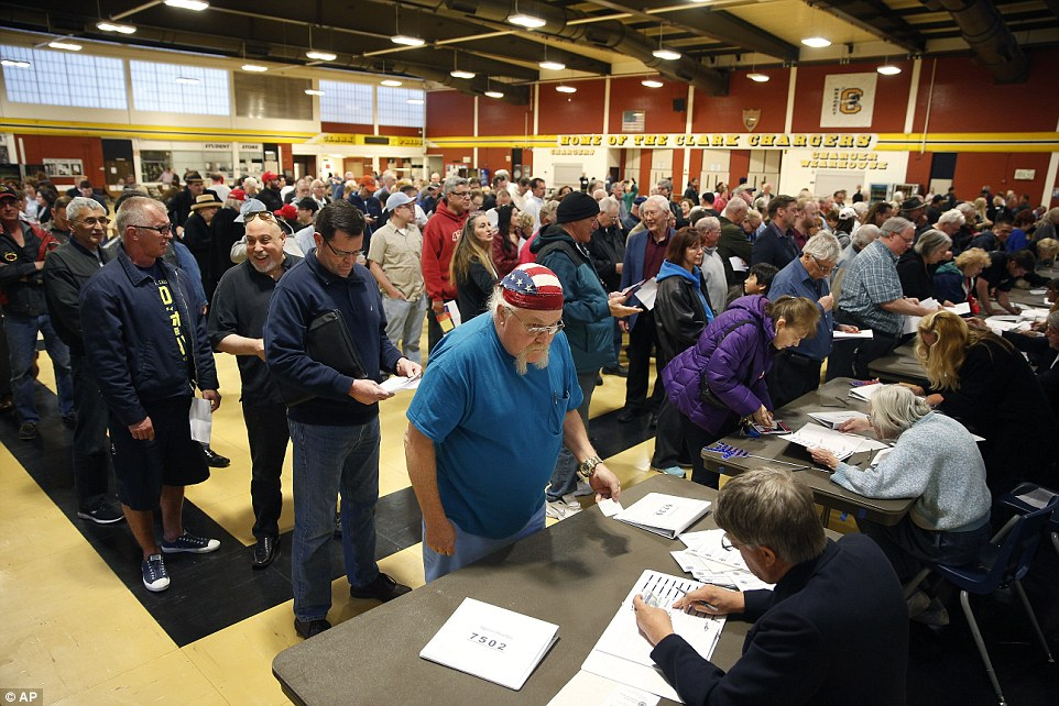 A long wait: Ballot shortages have been reported across a number of sites as turn out far exceeds what was predicted. Voters described the scenes as 'overwhelming' and 'very disorganized'