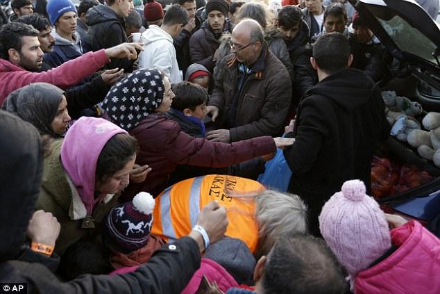 Refugiados y migrantes tratar de conseguir alimentos distribuidos por los voluntarios griegos después de su llegada desde las islas griegas del este al puerto del Pireo de Atenas '