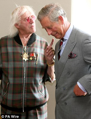 Friends in high places: Savile with Prince Charles