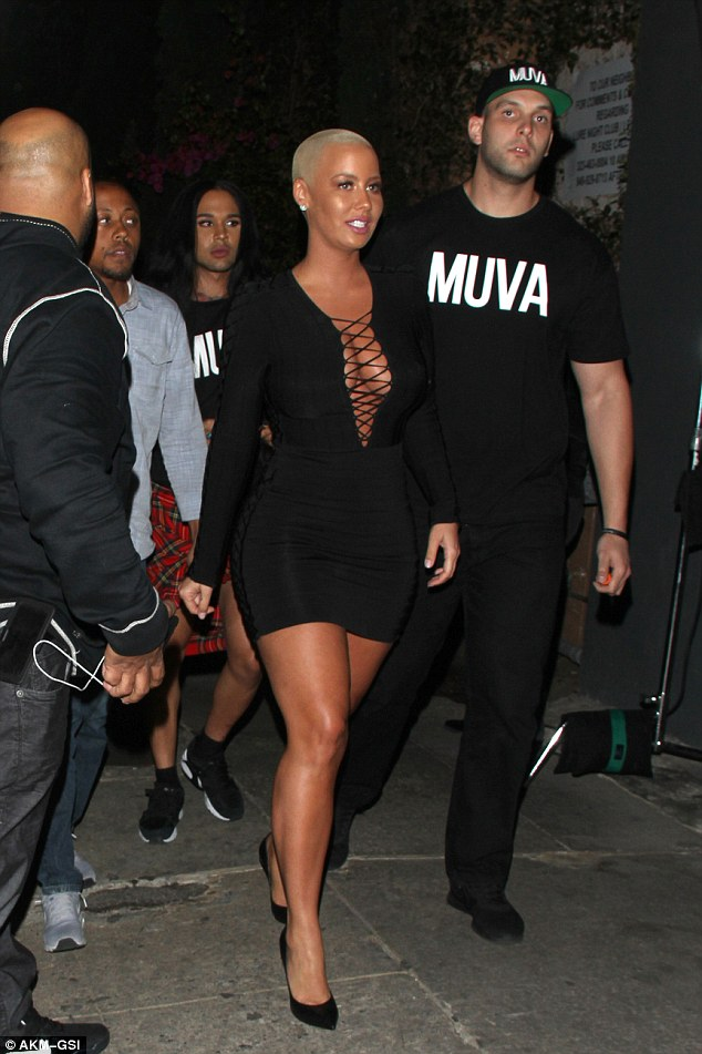 Her support team: As she later left the awards, she was flanked by a member of her entourage in a MUVA t-shirt, her nickname for herself