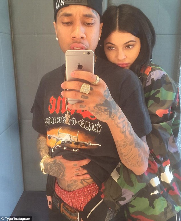 By his side: Girlfriend Kylie Jenner was spotted cuddling Tyga in a photo he posted to Instagram on Wednesday, as the star had traveled to his San Francisco show, sticking by his side through more financial woes