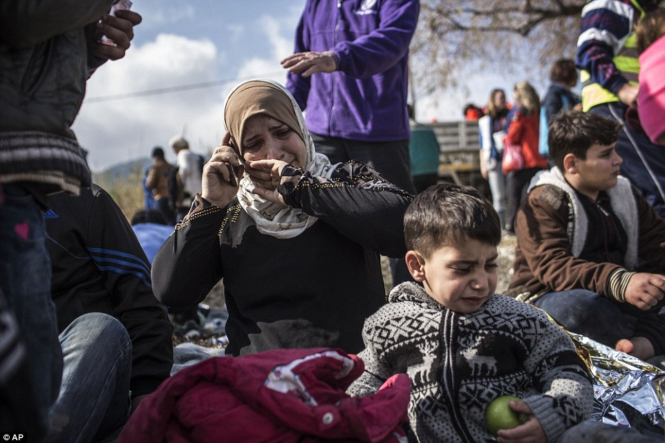 Long road ahead: A Syrian woman cries as she talks to her relatives after her arrival with other refugees and migrants from the Turkish coast to Greece