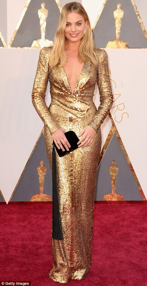 She's golden: Margot Robbie went for an extremely sexy look in a snakeskin style gold Tom Fordgown with low-cut neckline