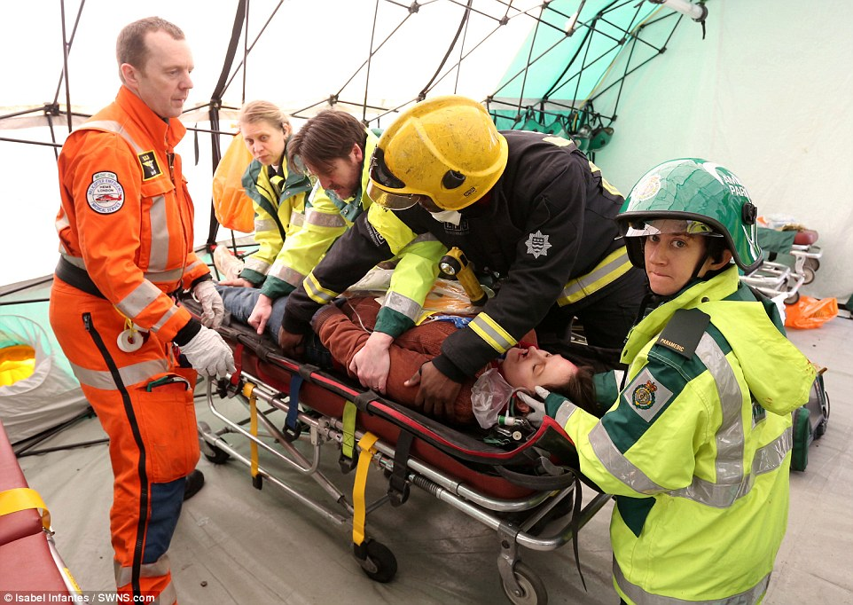 Emergency response: Workers from a number of different agencies are seen working together to treat a casualty recovered from the scene