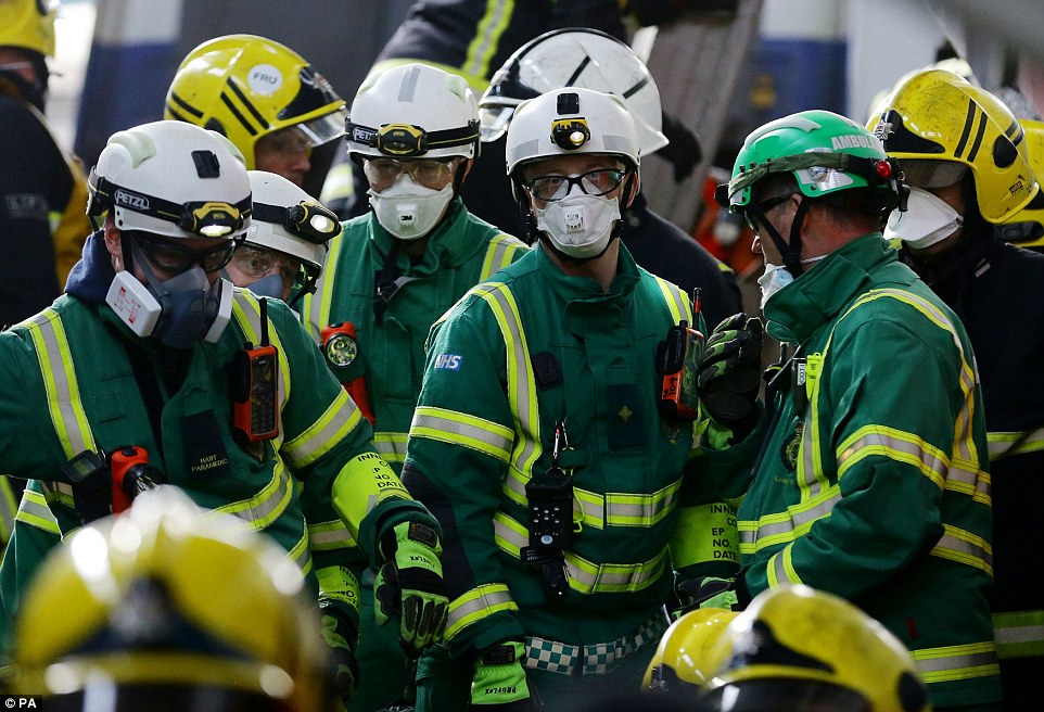 Moments away: Paramedics were dust masks to protect themselves as they tend to those caught up in the staged disaster