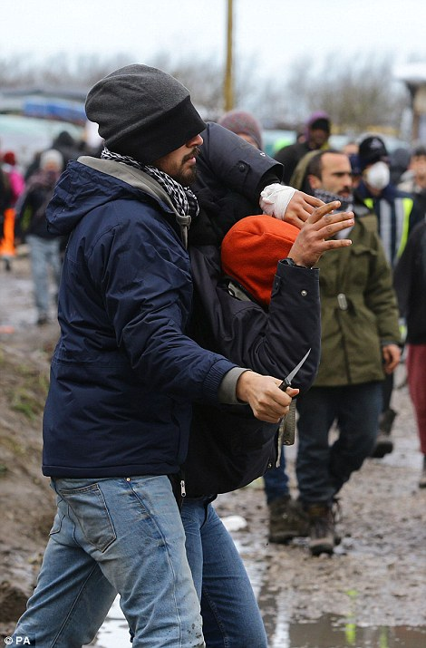 This was the scene as a migrant wielding a knife became embroiled in a fight amid violent scenes as French riot police continued their attempt to clear the Calais Jungle