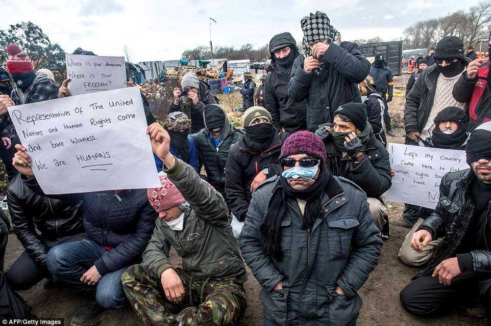 Demonstration: A group of migrants staged a sit-down protest in a bid to slow down the clear-up. Some held up signs saying 'We are humans'