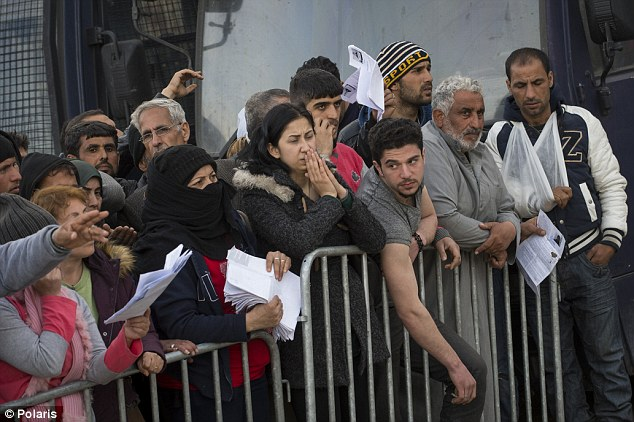 Refugees who hope to get on a waiting list to cross the border wait in line in Greece