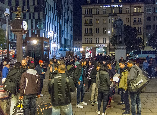 Unsettling: Groups of men gather outside Stockholm's railway station as commuters hurry past