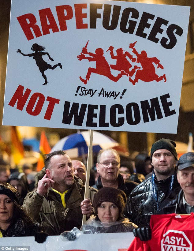 Pegida organiser Lutz Bachmann (left) holds a poster during a march of the right-wing group  in Leipzig in January. Germany. Pegida and other right-wing activists have been quick to latch on to the New Year's Eve sex attacks in Cologne to demand that Germany no longer accepts migrants into the country