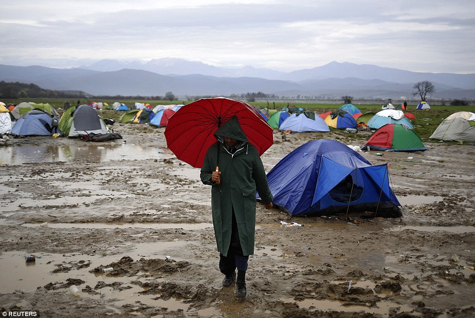A migrant waiting to cross the Greek-Macedonian border walks through a makeshift camp near the village of Idomeni, Greece