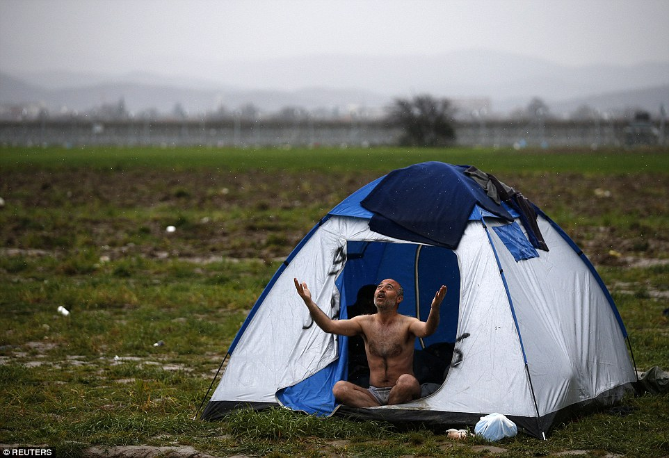 A migrant gestures while being photographed at a makeshift camp near the village of Idomeni on the Greek-Macedonia border
