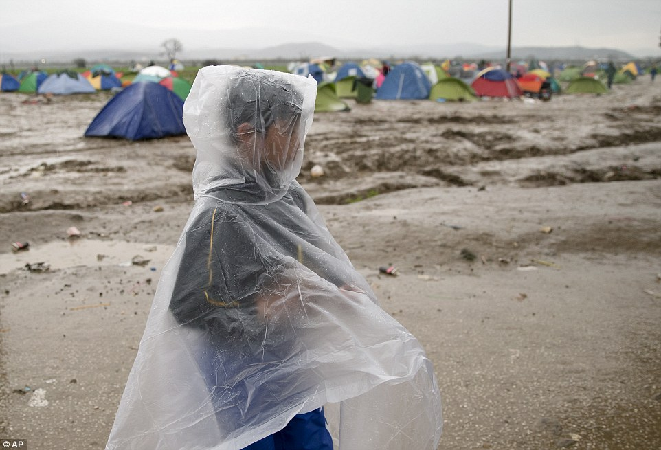 A migrant boy covered in a plastic poncho walks during rainfall at the northern Greek border station of Idomeni