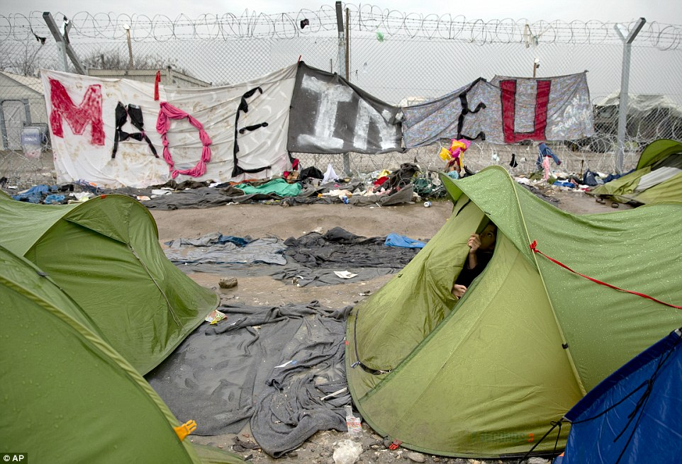 A child closes a tent by a banner placed on the enforced razor wire fence between Macedonia and Greece that reads 'Made in EU'